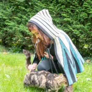 Cape avec capuche tricotée en laine de pays avec des motifs originaux.