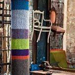 yarn bombing, recouvrement d'un poteau en tricot main de différentes couleurs.
